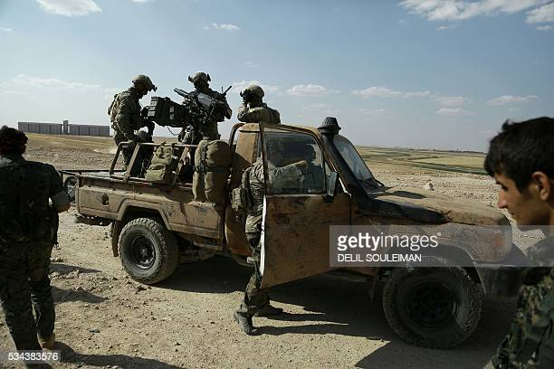 Armed men in uniforms identified by Syrian Democratic forces as US special operations forces stand in the back of a pickup truck in the village of...