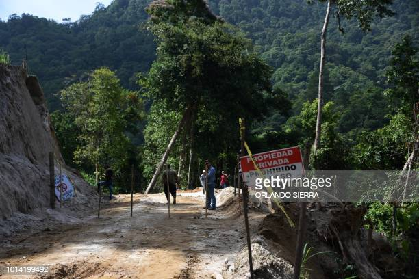 Armed men remain next to a sign reading Private Property Trespassing Prohibited near the Nombre de Dios mountain range where the Centrales El...
