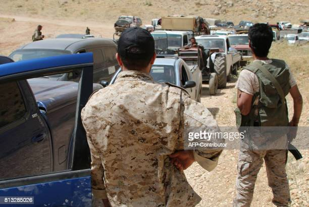 Armed men stand guard as a convoy of Syrian refugees leaves the Lebanese eastern border town of Arsal heading towards the Syrian region of Qalamoun...