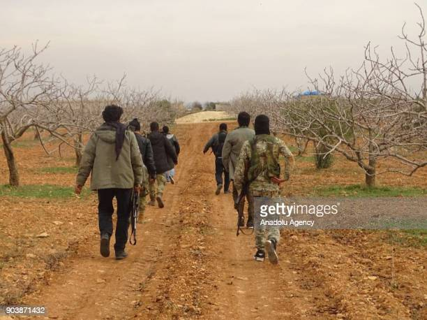 Armed men walk on a dirt road in Idlib Syria on January 11 2018 Assad Regime and its supporter terrorist groups continue their attacks in the...