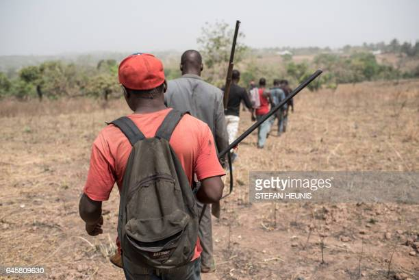 Armed men walk to the mass grave outside the village of Bakin Kogi in Kaduna state northwest Nigeria that was recently attacked by suspected Fulani...