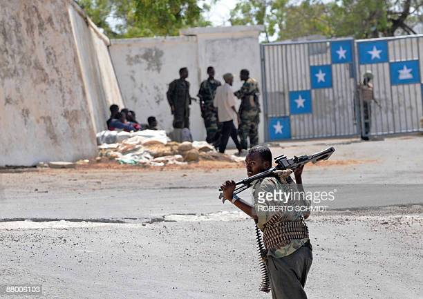 Armed men working for the transitional federal government stand outside the gate to the Somali President's house within the presidential compound...