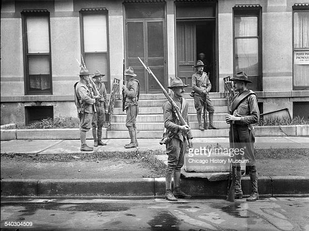 Armed National Guard standing outside apartments during the race riots in Chicago Illinois 1919