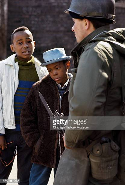 Armed National Guardsman standing in front of two African American boys around the time of the riots that broke out in South and West Side...
