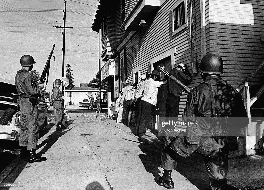 Armed National Guardsmen force a line of Black men to stand against the wall of a building during the Watts race riots, Los Angeles, California, August 1965.