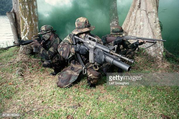 armed navy seals camouflaged by smoke - navy seals de los estados unidos fotografías e imágenes de stock