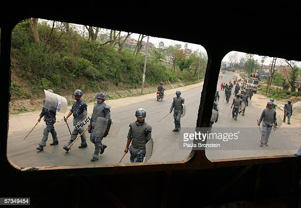 Armed Nepalese police patrol the empty streets as seen through a burned bus as a ban on protesting in the center of Kathmandu prevents large...
