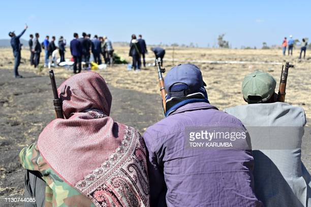 Armed Oromo tribesmen look on as a family of Chinese nationality visit the crash site of the Ethiopian Airlines operated Boeing 737 MAX aircraft in...