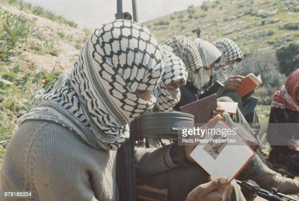 Armed Palestinian fighters of the Fatah faction of the Palestine Liberation Organisation pictured reading copies of Quotations from Chairman Mao...