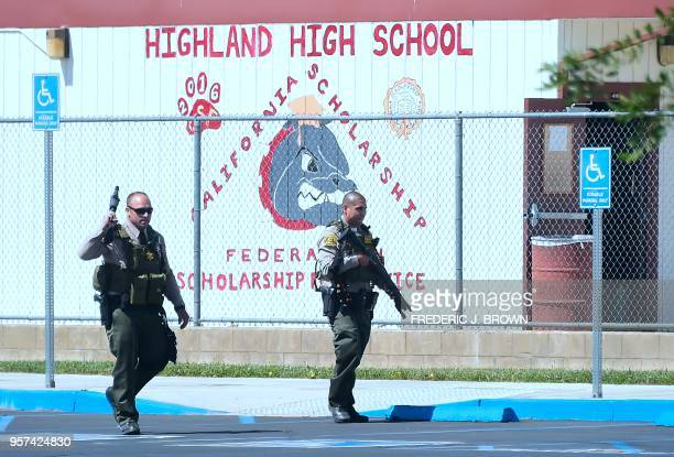 TOPSHOT Armed personnel from the sheriff's department walk around the campus on May 11 2018 following reports of shooting at Highland High School in...