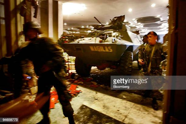 Armed Philippine troops enter the Peninsula Hotel after using an armored personnel carrier to break through the doors of the hotel where Senator...