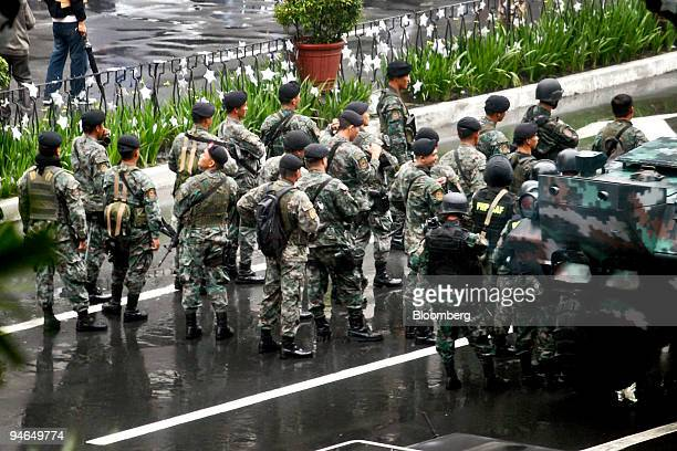 Armed Philippine troops move along Ayala Avenue as they approach the Peninsula Hotel where Senator Antonio Trillanes and General Danilo Lim were...