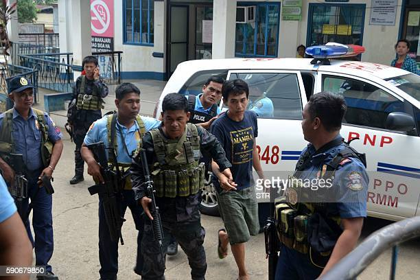 Armed Philippines policemen escort Indonesian national Muhamad Sofyan into a police station in Jolo town Sulu province in southern island of Mindanao...