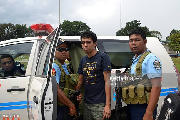 Armed Philippines policemen escort Indonesian national Muhamad Sofyan as they leave a hospital in Jolo town Sulu province in southern island of...