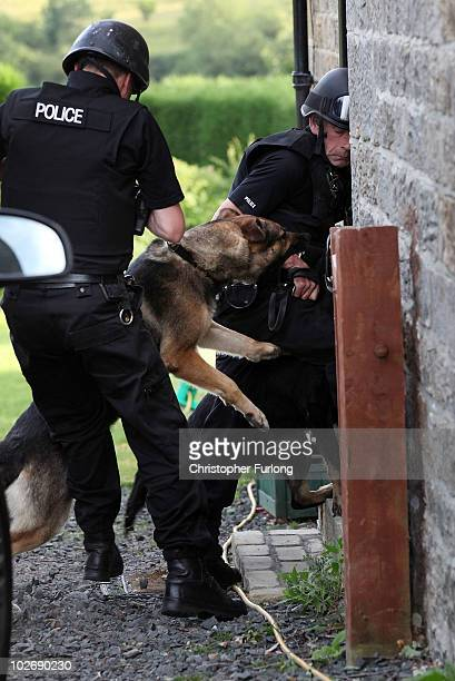 Armed police and an attack dog search Priorsgate Cottage in the village of Rothbury as the search for armed fugitive Raoul Moat goes on in the...