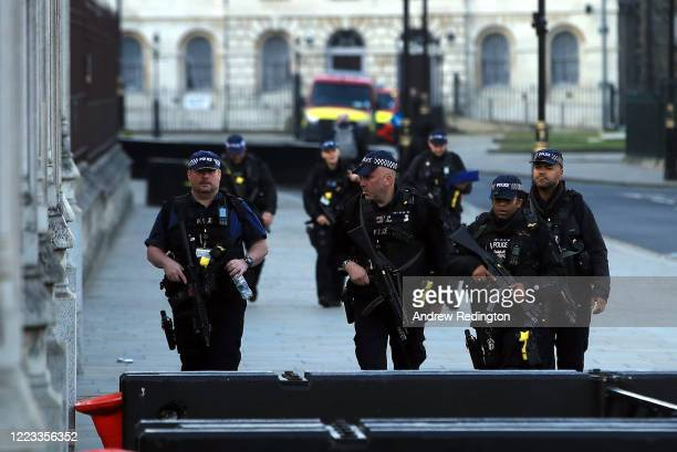 Armed police are pictured outside the Houses of Parliament on May 07, 2020 in London, England. The UK is continuing with quarantine measures intended...