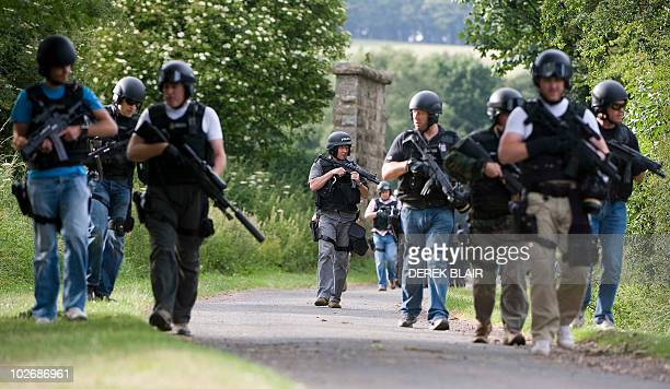Armed police can be seen in the woods around Rothbury at Wagtail Farm in the continued search for Raoul Moat, in Rothbury, northeast England on July...