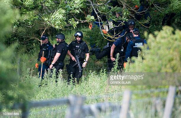 Armed police can be seen in the woods surrounding Rothbury in the continued search for Raoul Moat, in Rothbury, northeast England on July 7, 2010....