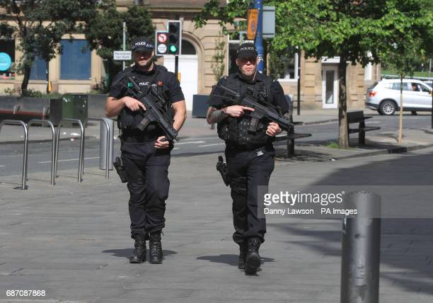 Armed police close to the Manchester Arena the morning after a suicide bomber killed 22 people including children as an explosion tore through fans...