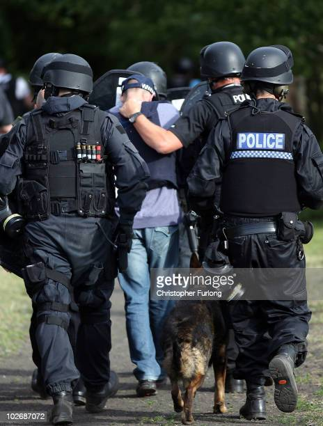 Armed police escort a man along a track near Wagtail Farm in the village of Rothbury as the search for armed fugitive Raoul Moat goes on in the...