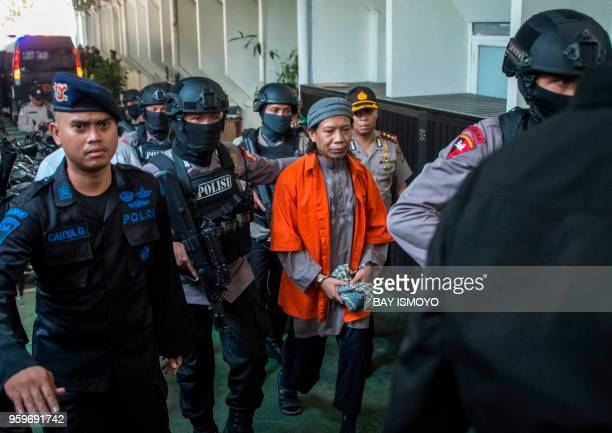 Armed police escort Aman Abdurrahman leader of the Islamic State group linked militant outfit Jamaah Ansharut Daulah to a court hearing for the...