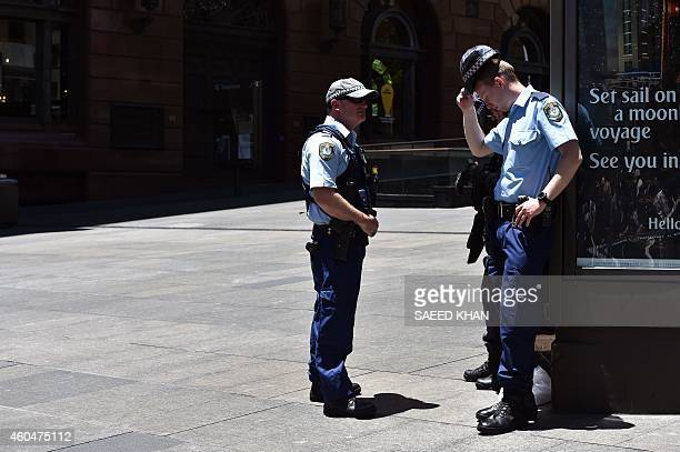 Armed police evacuate employees from the offices next to a cafe in the central business district of Sydney on December 15 2014 Hostages were being...