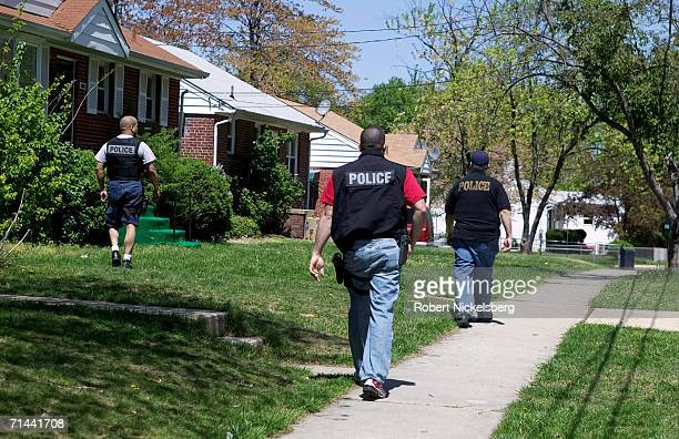 Armed police from Maryland's Prince George's County AntiGang Unit stake out a house for a wanted street gang member of Mara Salvatrucha 13 or MS13...