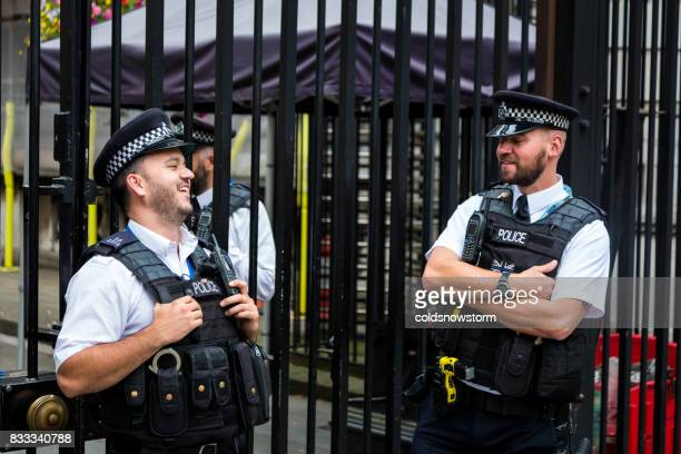 Armed police laughing and smiling outside Downing Street in central London, UK