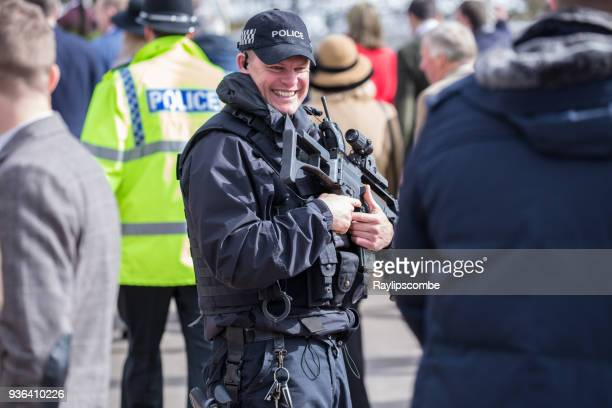 armed police officer, laughing with the crowds on their way to famous cheltenham festival national hunt races - police taser stock pictures, royalty-free photos & images