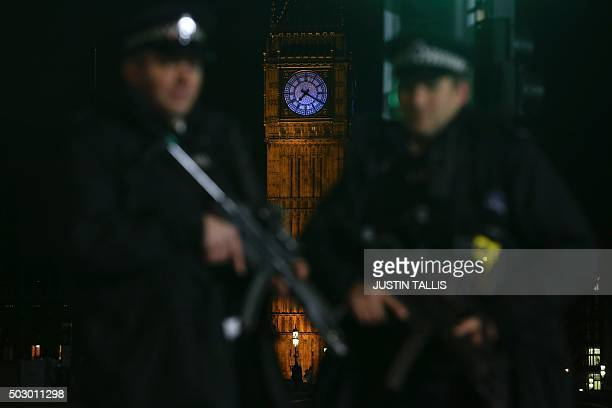 Armed police officer patrol with Elizabeth Tower in the background ahead of the New Year's Eve fireworks in London on December 31 2015 British police...