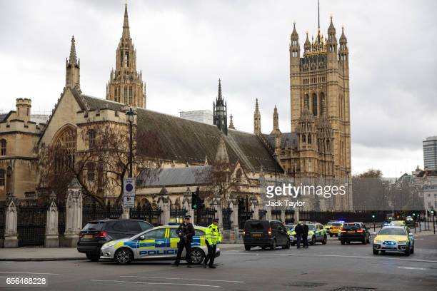 Armed police officer stand guard near Westminster Bridge and the Houses of Parliament on March 22 2017 in London England A police officer has been...