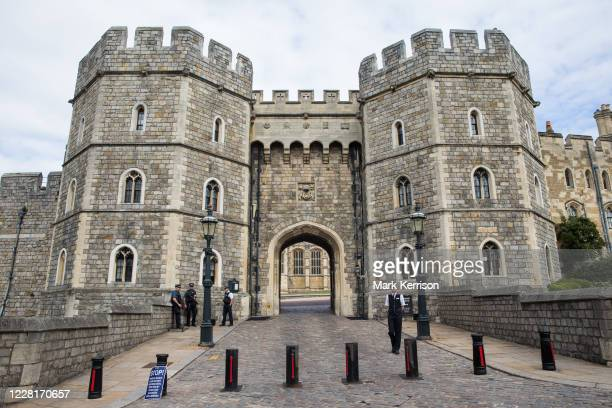 Armed police officers and a warden offer security and assistance outside the Henry VIII Gateway at Windsor Castle on 23rd August 2020 in Windsor,...