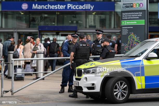 Armed police officers and dog units stand guard outside Piccadilly train station on May 24 2017 in Manchester England An explosion occurred at...
