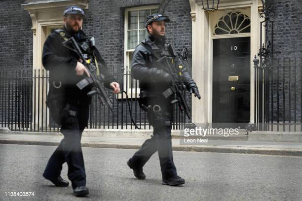 Armed police officers are seen through a railing as they walk along Downing Street following a cabinet meeting on March 26 2019 in London England...