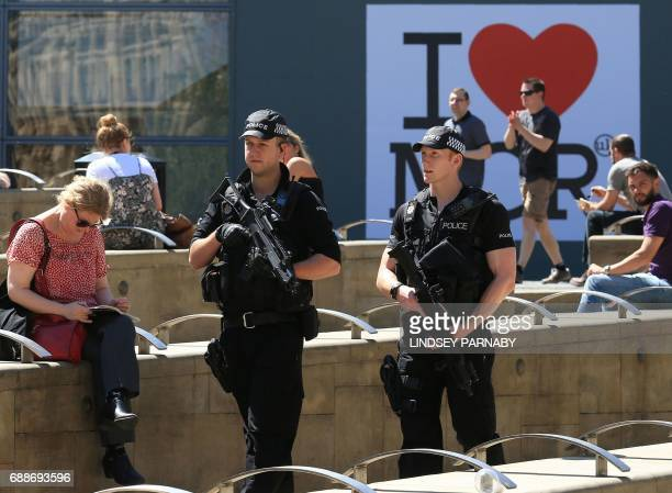 Armed police officers carry their weapons as they pass an I Love MCR symbol in Manchester northwest England on May 26 2017 Britain is hunting for a...