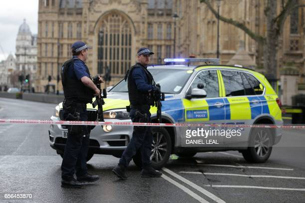 Armed police officers guard at a police cordon outside the Houses of Parliament in central London on March 22 2017 during an emergency incident / AFP...