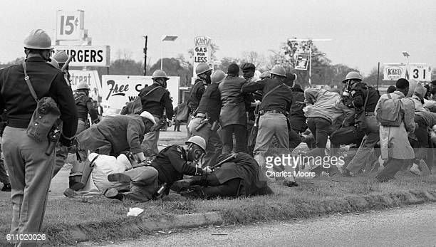 Armed police officers in gas masks charge at demonstrators at the base of the Edmund Pettus Bridge during the first Selma to Montgomery March, Selma,...