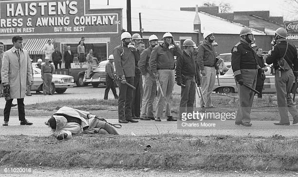 Armed police officers in gas masks stand by the unconscious body of Civil Rights activist Amelia Boynton at the base of the Edmund Pettus Bridge...
