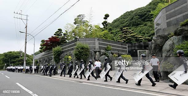 Armed police officers leave the headquarters of Japanese yakuza organization Kudokai after a raid on June 6 2014 in Kitakyushu Fukuoka Japan The...
