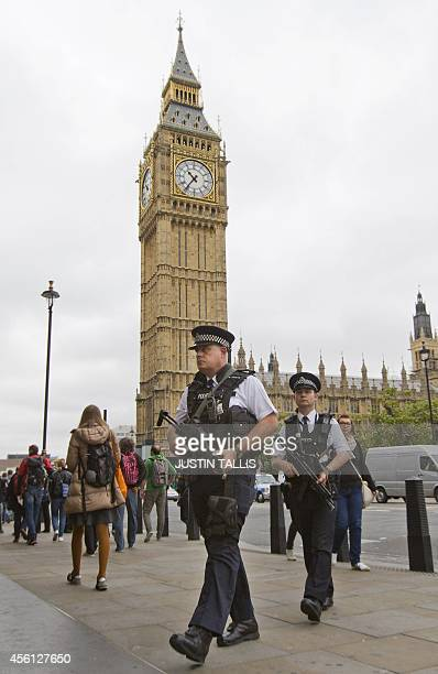Armed police officers patrol a street outside the Houses of Parliament where lawmakers are expected to vote in favour of joining air strikes against...