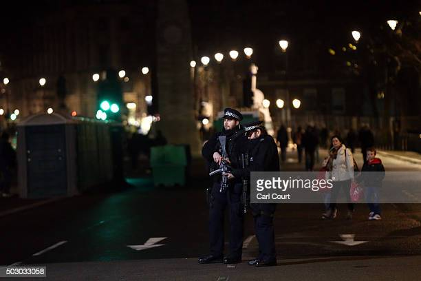 Armed police officers patrol ahead of the fireworks on December 31 2015 in London England Thousands of people have bought tickets to stand on the...
