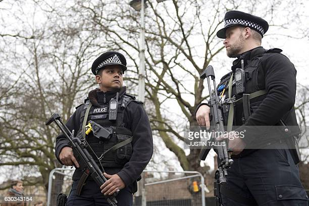 Armed police officers patrol outside Buckingham Palace in central London on December 21 2016 before the Changing of the Guard ceremony Roads in front...