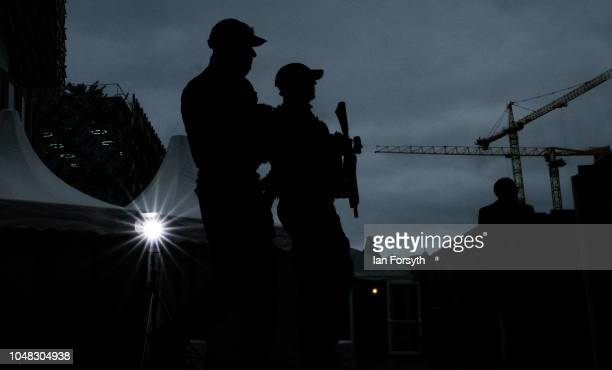 Armed Police officers patrol past a television news light as they maintain security at the International Convention Centre on day three of the...