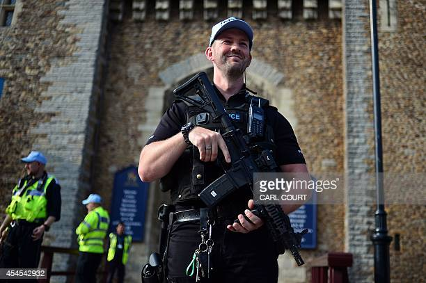 Armed police officers patrol the area outside the entrance to Cardiff Castle in Wales on September 3 on the eve of the 2014 NATO Summit Some 67 world...