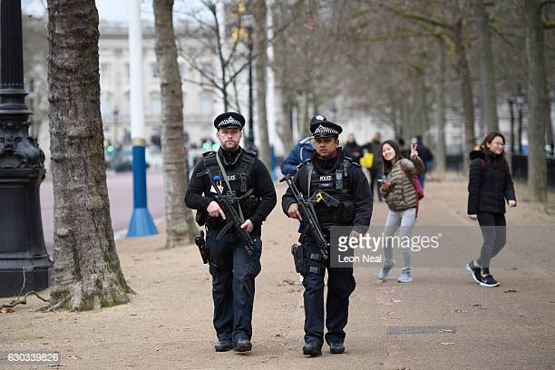 Armed police officers patrol The Mall in front of Buckingham Palace ahead of the Changing of the Guard ceremony on December 21 2016 in London England...