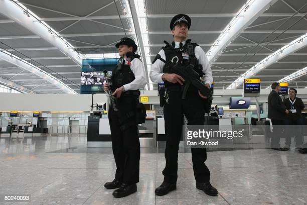 Armed police officers patrol the new Terminal 5 at Heathrow Airport prior to its official opening on March 14 2008 in London England The £43 billion...