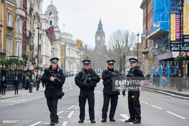 Armed police officers secure the area on Whitehall leading toward the Houses of Parliament in central London on March 23 2017 the day after the March...
