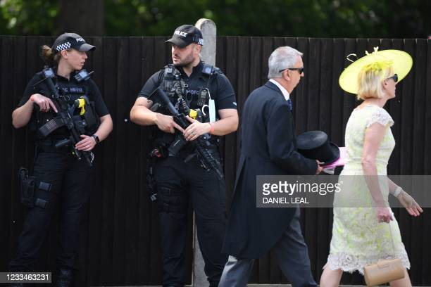 Armed police officers stand guard as race-goers arrive on the first day of the Royal Ascot horse racing meet, in Ascot, west of London on June 15,...