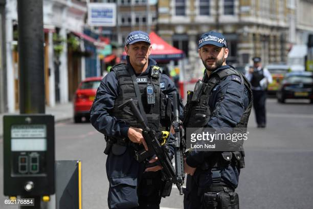 Armed police officers stand guard at the perimeter cordon following last night's London terror attack on June 4 2017 in London England Prime Minister...