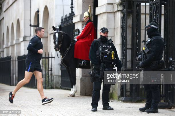Armed police officers stand guard by a member of the Household cavalry on Whitehall as England enters a second coronavirus lockdown on November 5,...